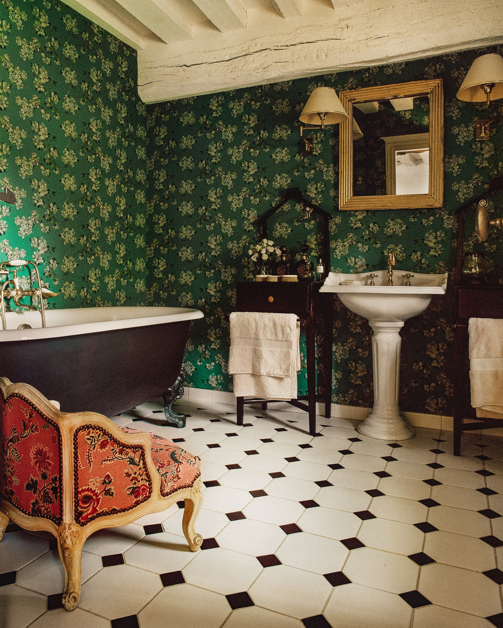 A wallpapered bathroom in Cordelia de Castellanes French country home.